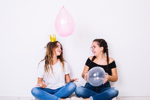 Sitting teenagers playing with balloons