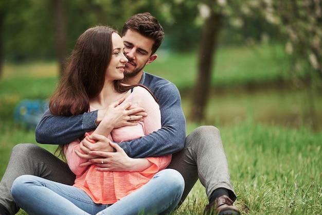 Весной вместе сидеть на свежем воздухе. молодая пара обнимая