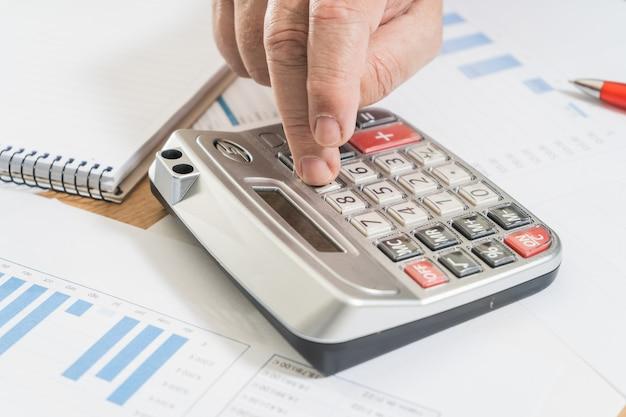 電卓で会計をしている白人男性に座って、現金とお金の流れ、予測、請求書を確認します。在宅勤務、当座預金口座、家の経済。