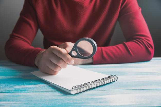 ノートを見て虫眼鏡で座って