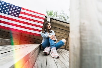 Sitting woman and american flag