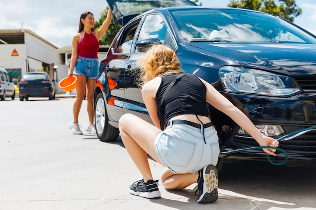 Sitting woman inflating tire while other female opening trunk