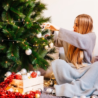 Sitting woman is next to christmas tree