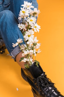 Sitting womans legs in boots with flowers bouquet inside