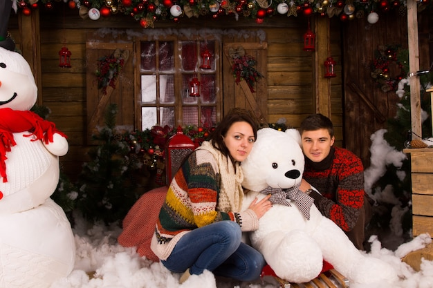 겨울 의상을 입은 젊은 부부는 큰 눈사람과 다양한 크리스마스 장식으로 장식된 목조 주택에서 하얀 겨울 곰 인형을 껴안고 있습니다.