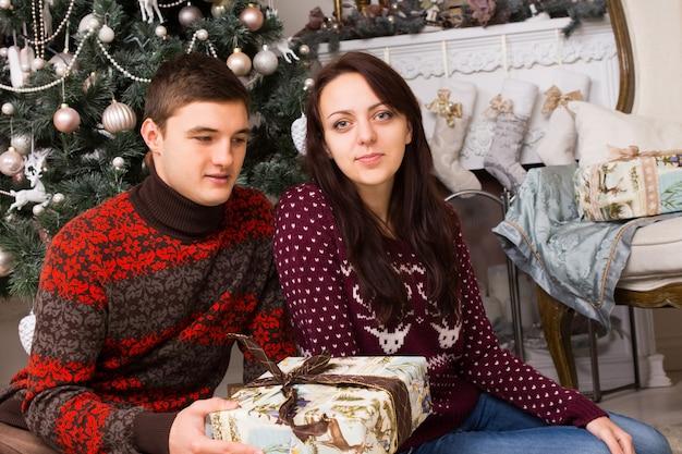 さまざまな装飾品が付いたクリスマスツリーの近くに、ギフトボックス付きのカジュアルな冬のシャツを着た若い白人の友達が座っています。