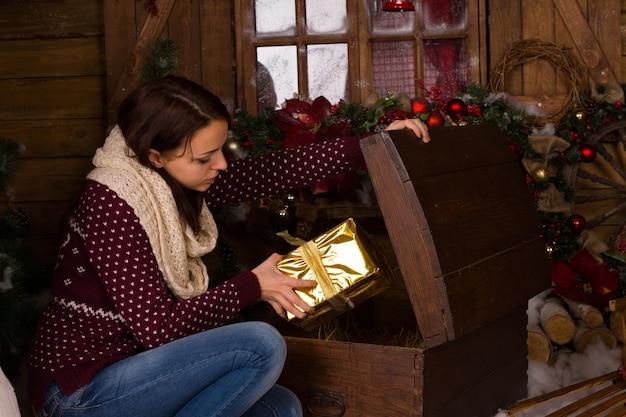 座っている若い女性がヴィンテージの木製トランクからゴールデンクリスマスプレゼントボックスを取得します。