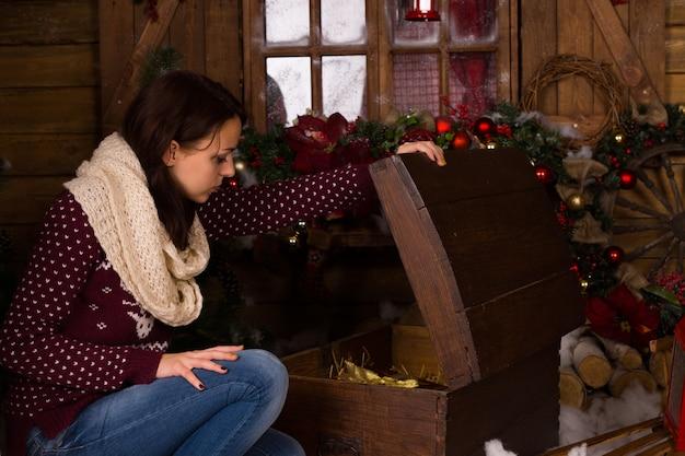 トレンディな冬の衣装で若い女性に座って、クリスマスの装飾が施された家の中でヴィンテージの木製トランクを開きます。