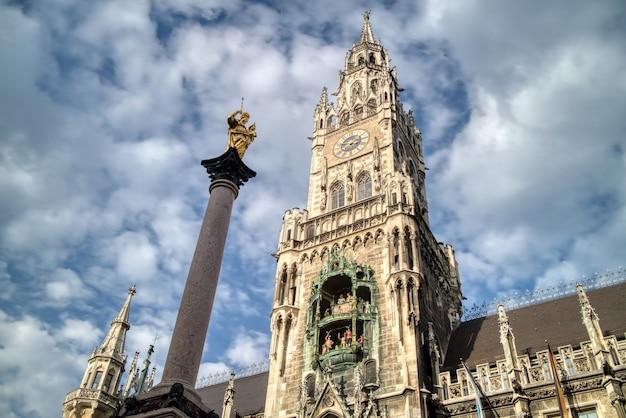 Городской пейзаж с колонной святой марии и новой ратушей на площади мариенплац на фоне голубого облачного неба, мюнхен, бавария, германия