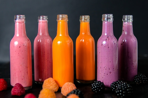 Six bottles with smoothies and raspberry, red, yellow, blackberry on black background