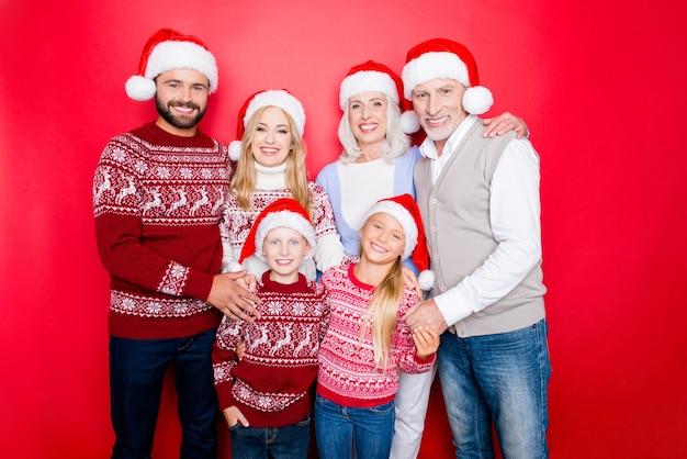 赤いスペースに孤立した6人の白人の親戚、夫婦、興奮した兄弟、おじいちゃん、おばあちゃん、ニットのかわいい伝統的なクリスマスの衣装、ジーンズ、抱きしめる、一体感、一体感