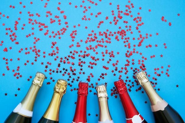 水色の背景に紙吹雪の星が付いた6本のシャンパンボトル。クリスマス、記念日、独身、新年のお祝いのコンセプトのフラットレイ。コピースペース、上面図