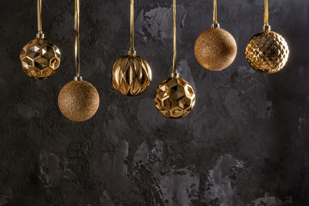 Six christmas balls of golden color are hanging by a ribbon.