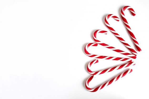 Six christmas lollipops, new year's red and white candies in the shape of a cane are fan-shaped on a white background