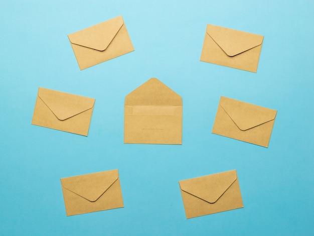 Шесть закрытых и один открытый почтовые конверты на синем фоне. плоская планировка.