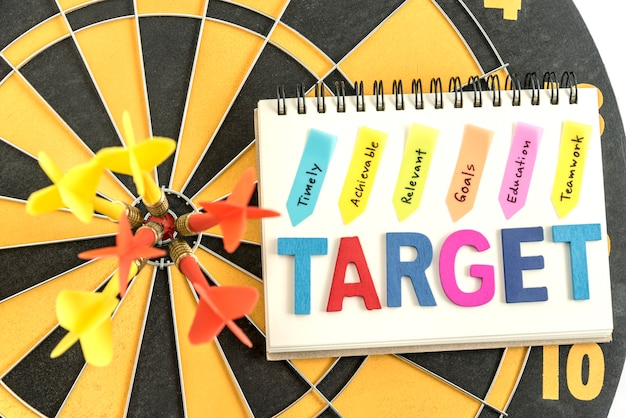 Six dart in bullseye with words target on the notebook with handwriting timely achievable relevant goals education teamwork over dartboard background, business success concept