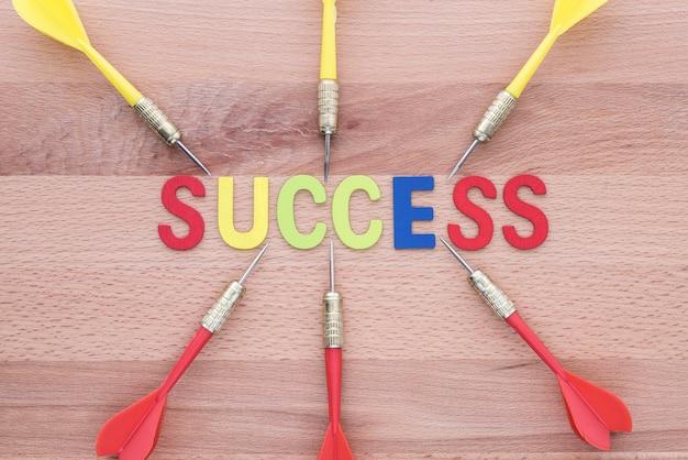 Шесть дротиков вбегают в цель успеха на деревянном фоне