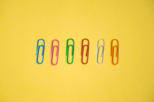 Шесть разноцветных скрепок на желтом фоне для использования отдельно или в качестве элемента дизайна
