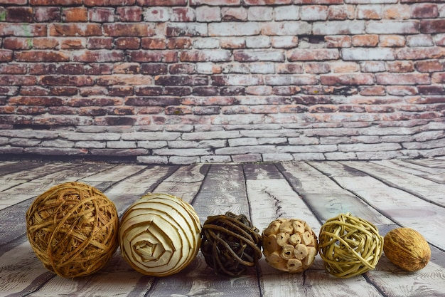 Six different types, colors and composition of wicker decorative balls lie in a row on a wooden old background and a brick wall at the bottom of the frame