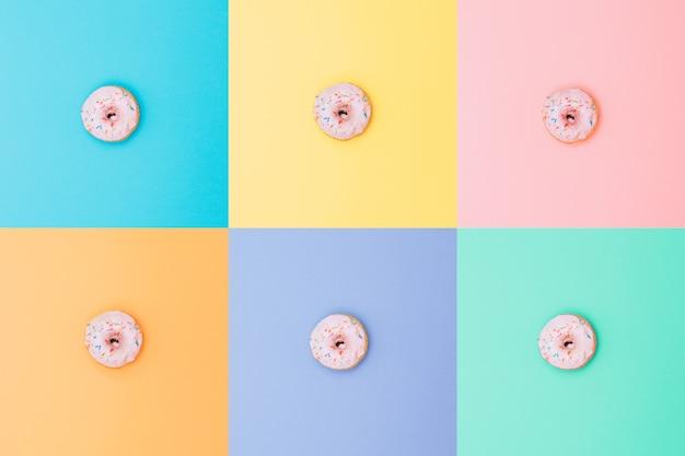 팝 아트와 미니멀리즘 스타일의 다른 배경에 있는 6개의 동일한 분홍색 도넛.