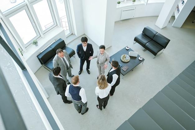作業ポイントや契約条件の議論中にオフィスに立っている間、正装を作るサークルの6人の異文化間の同僚