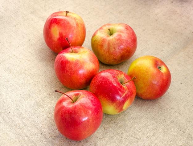 Шесть сочных, красивых, больших красных яблок на белом фоне.