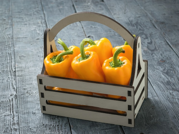 Six large ripe peppers in a wooden box on a wooden table. vegetarian food.