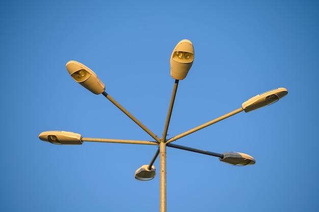 Шесть светодиодных уличных фонарей на высоком металлическом столбе в желтом вечернем свете заката