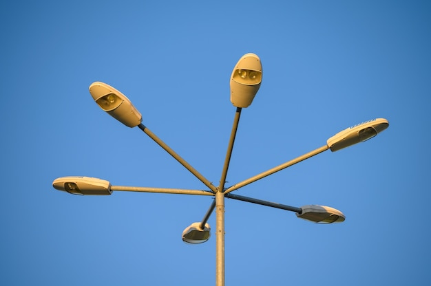 Six led street lamps at tall metal post in the yellow evening light of sunset