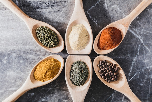Six light wooden spoons with colorful spices