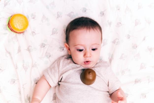 おもちゃの果物と這うキルトの上に横たわっている生後6ヶ月の赤ちゃん