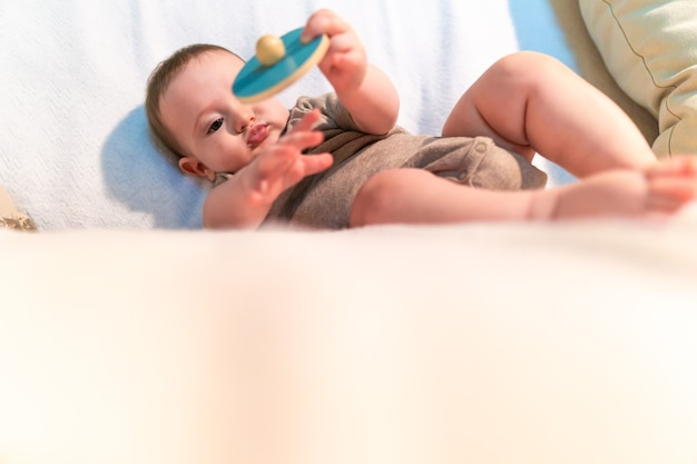 Six month old baby playing with a montessori wooden toy