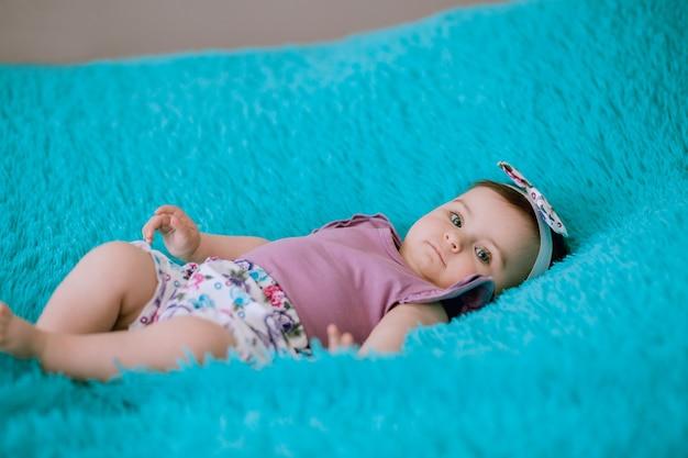 Шестимесячный ребенок в пурпурном платье лежит на голубой кровати и внимательно смотрит в камеру