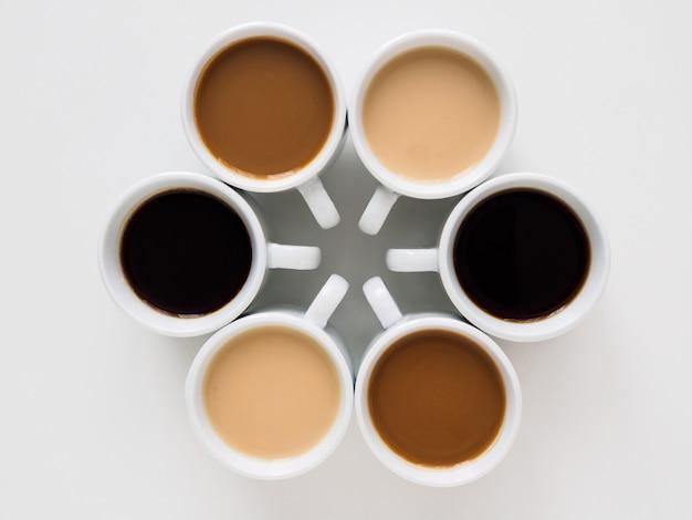 Шесть кружек разного кофе выстроились в виде снежинок.