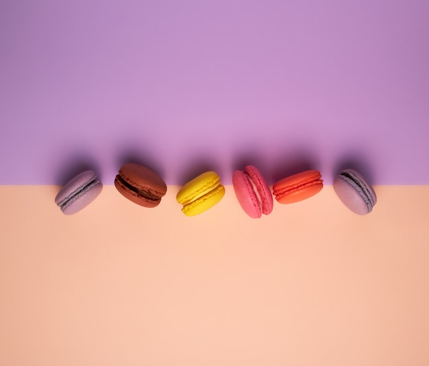 Six multi colored macarons with cream background