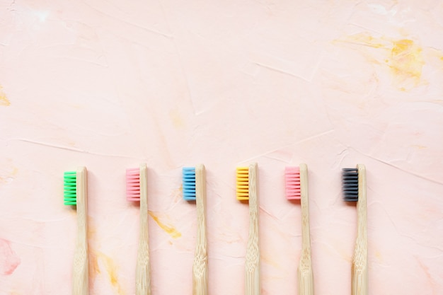Six natural wooden bamboo toothbrushes. plastic free and zero waste concept. top view, pink backgroundon, copy space