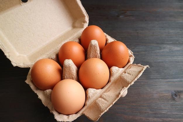 暗い木の表面の紙箱の有機鶏卵の6つ