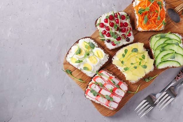 Шесть бутербродов на тосте со свежей морковью, огурцами, ананасом, красной смородиной, крабовыми палочками и перепелиными яйцами с микрозеленью гороха на деревянной доске на сером фоне, вид сверху, копией пространства