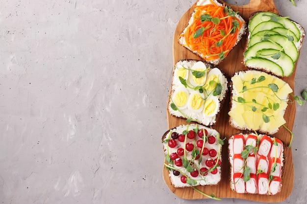 新鮮なニンジン、きゅうり、パイナップル、赤スグリ、カニカマ、ウズラの卵とトーストの6つのサンドイッチ、灰色の表面の木製ボードにエンドウ豆のマイクログリーン、上からの眺め、テキスト用のスペース