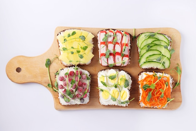 Six sandwiches on toast with fresh carrots, cucumbers, pineapple, red currant, crab sticks and quail eggs with microgreens on wooden board
