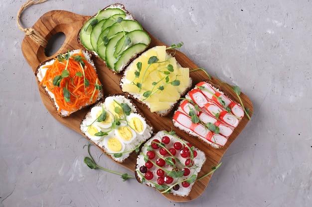 Шесть бутербродов со свежей морковью, огурцами, ананасом, красной смородиной, крабовыми палочками и перепелиными яйцами с микрозеленью гороха на деревянной доске на серой поверхности