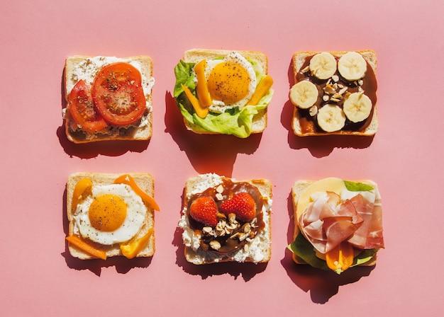 Шесть бутербродов с помидорами, омлетом, шоколадом, ветчиной и сыром на розовой поверхности. вид сверху