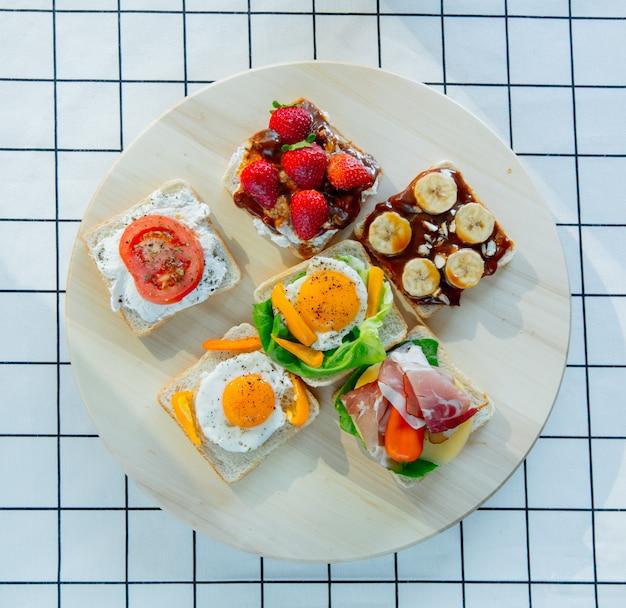 Шесть бутербродов с помидорами, омлетом, шоколадом, ветчиной и сыром на деревянном столе .. вид сверху