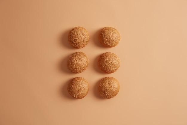 베이지 색 스튜디오 배경에 두 줄로 배열 된 6 개의 참깨 버거 빵. 수제 브리오슈는 디너 롤로 사용됩니다. 집에서 요리사가 만든 빵. 아침에 맛있는 음식. 오버 헤드 높은 각도보기