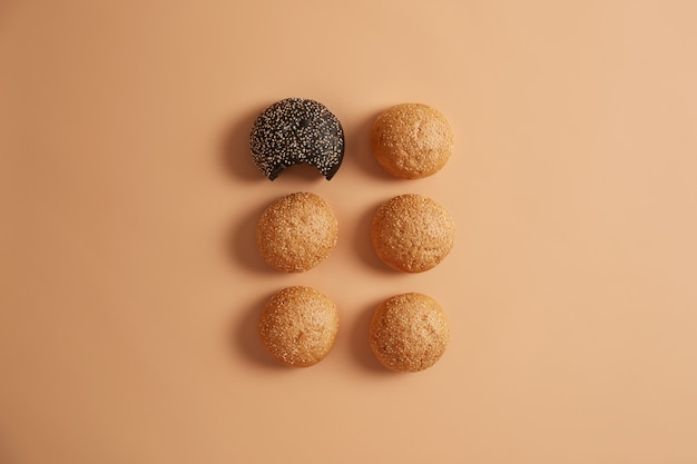 Six small round burger buns made of yeast dough with sesame seeds on beige background. bakery products for making hamburger. unhealthy nutrition concept. one black roll is bitten. fresh food