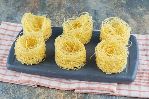 Шесть стопок тонких спагетти на доске, на полотенце, на мраморной поверхности.