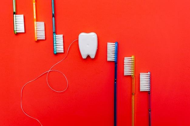 Шесть зубных щеток в необработанном виде возле игрушечного зуба. красный фон. стоматологическая концепция.