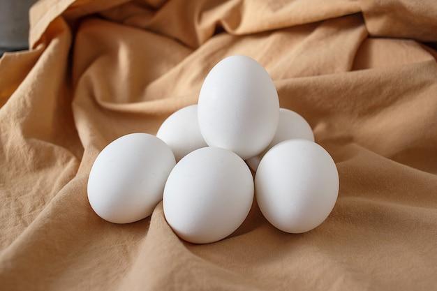 Six white chicken eggs on beige background