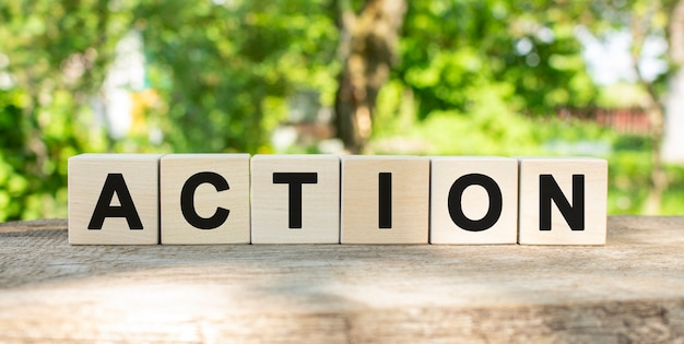 Six wooden blocks lie on a wooden table against the backdrop of a summer garden and create the word action. concept for your design
