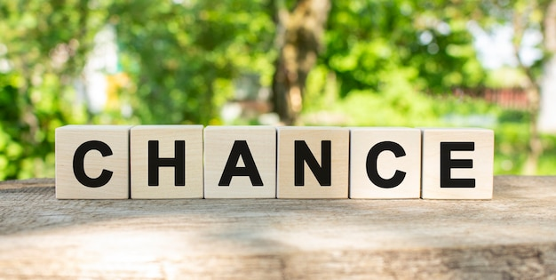 Six wooden blocks lie on a wooden table against the backdrop of a summer garden and create the word chance. concept for your design